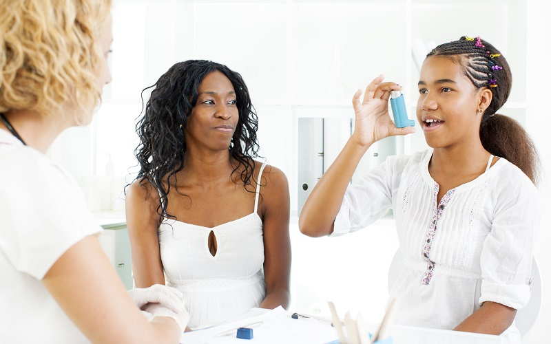 A young African-American girl holding an inhaler while a doctor guides her on using it.