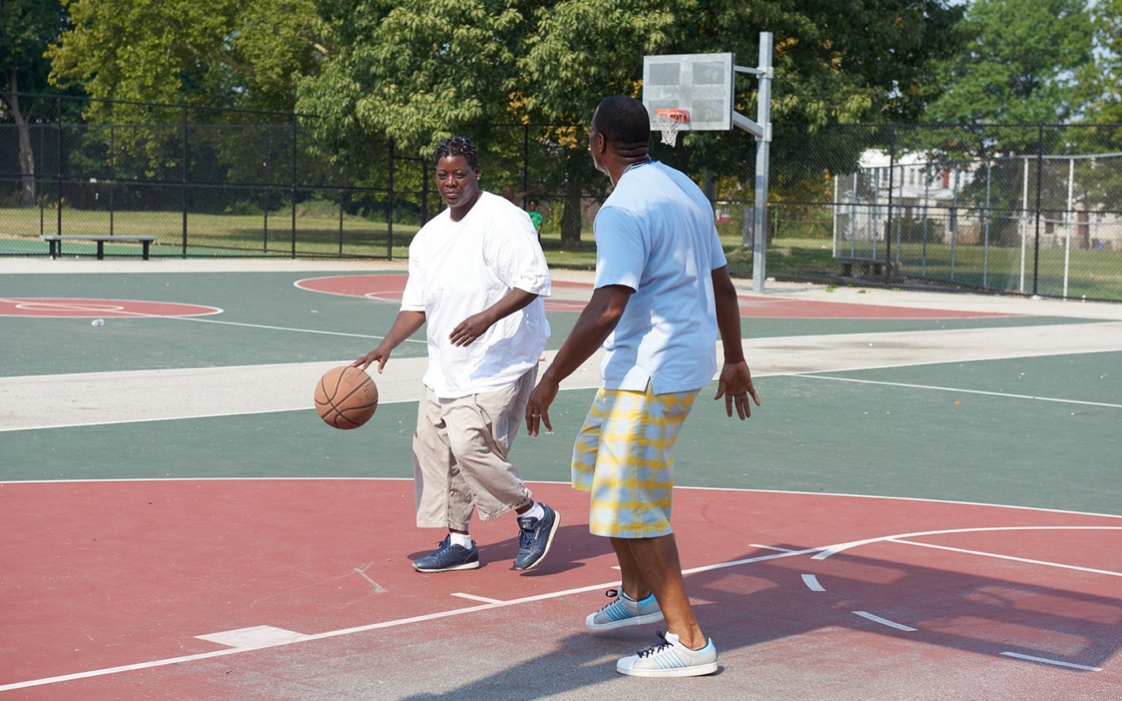 A community health worker plays basketball with a patient