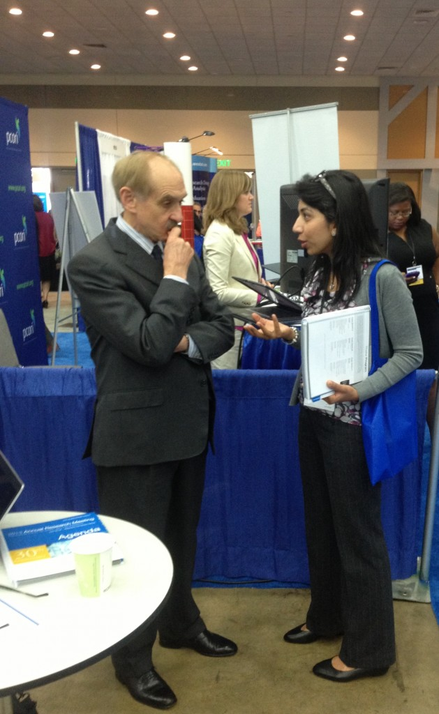 Bryan Luce speaking to a visitor at the PCORI booth during the Academy Health convention